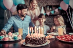 Happy family is sitting at the table in decorated kitchen during birthday celebration, birthday cake in the foreground